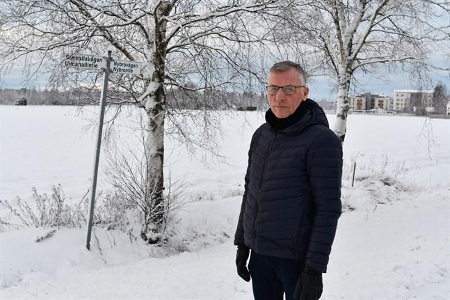 Olav Sjögård hoppas att Skarpängsvägen byggs snart. Nybrovägen byter namn till Simhallsvägen ungefär där Skarpängsvägen kommer att korsa vägen. Traktorn till vänster i bild kör på Kristinestadsvägen. Åkrarna bakom Sjögård ska blir bostadsområde.
