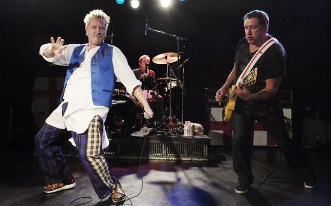 Johnny Rotten, med mikrofon i hand, Paul Cook vid trummorna och Steve Jones med gitarr runt halsen vid en Sex Pistols-konsert 2007.
