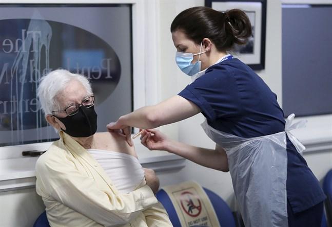 John Elphinstone får en dos av Astra Zenecas vaccin mot covid-19 på Pentlands Medical Centre i Edinburgh, Skottland. Sju nya stora vaccineringscentrum öppnar i Storbritannien under måndagen.