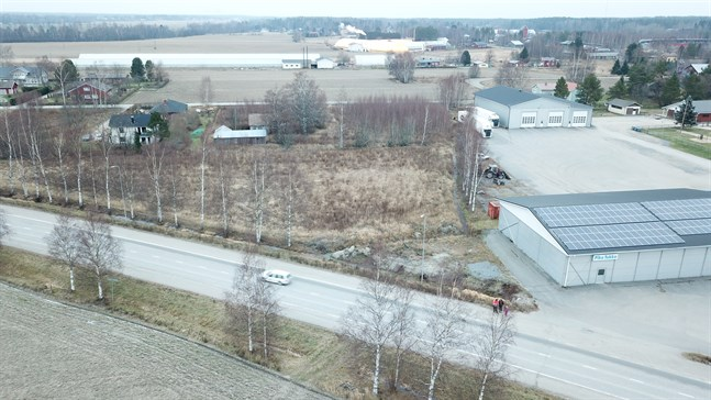 Skarpängsvägen ska enligt planerna korsa Nybrovägen där den vita bilen kör och gå till vänster om Ekroos garage och till höger om det långa växthuset och fortsätta över åkrarna till Närpesvägen.