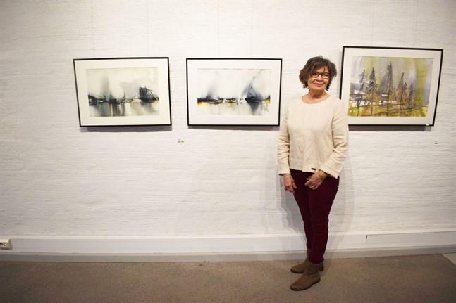 """Kerstin Sunabacka med målningarna """"Peace at the Port"""", """"Down by the river"""" och """"Nousihan Suomi - Finland"""" som alla är en del av utställningen """"Av luft och ljus""""."""