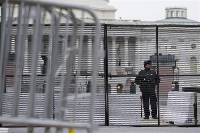 En polisman vaktar ett avspärrat Capitolium i Washington DC, efter stormningen förra veckan. Nödläge har utlysts i staden inför Joe Bidens installation den 20 januari.