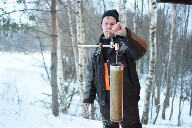 Anders Westerberg väger snön med hjälp av cylinder och våg.