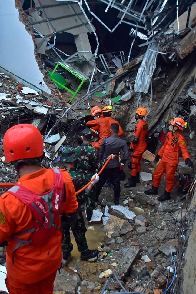 Räddningstjänsten söker överlevande som begravts under en byggnad som rasat i Mamuju i Indonesien.
