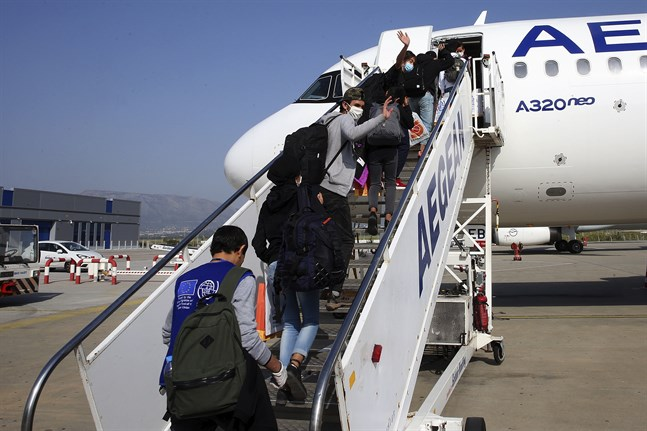 Ensamma barn som har suttit i överfulla migrantläger i Grekland kliver på ett plan i Aten som ska ta dem till Luxemburg, den 15 april 2020. Antalet internationella migranter minskade med 30 procent i fjol.