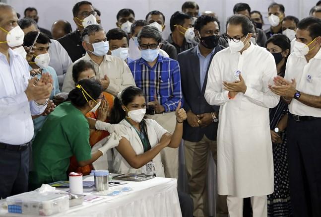 Sjukvårdaren Madhura Patil får sin vaccinspruta i Bombay under lördagen. Delstaten Maharashtras högste minister, Uddhav Thackeray, (till höger i vitt), deltog för att uppmärksamma att Indien nu börjar vaccinera sina medborgare i stor skala.