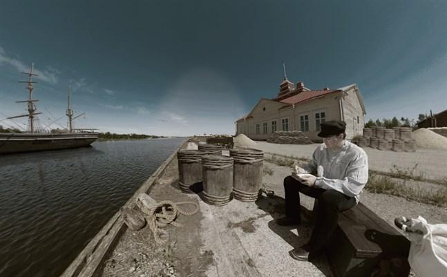Benjamin Kalliomäki gestaltar en sjöman som sitter på kajen och skriver brev. Fotot är taget i inre hamnen i Kristinestad.