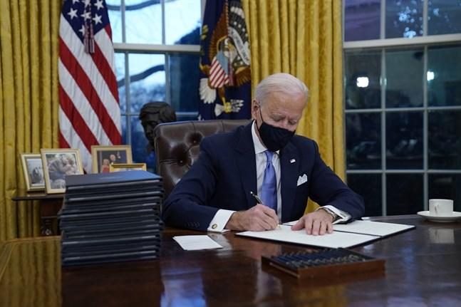 USA:s nye president Joe Biden undertecknar presidentordrar i Ovala rummet.