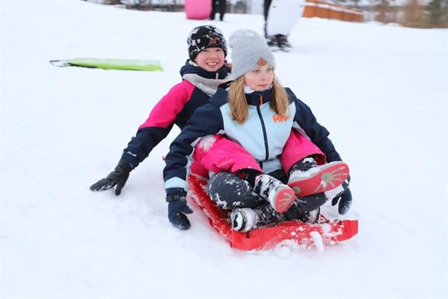 Linnea Kenni och Ella Kotimäki säger att madrassen är det bästa att ha med till pulkabacken – den är överlägset snabbast.