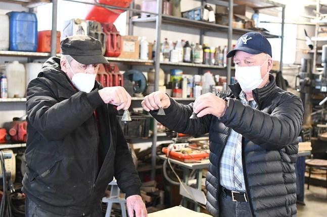 Gilbert Nyberg och Charlie Nyberg håller upp några av de bjällror de hittat. De har hängt runt halsen på får.