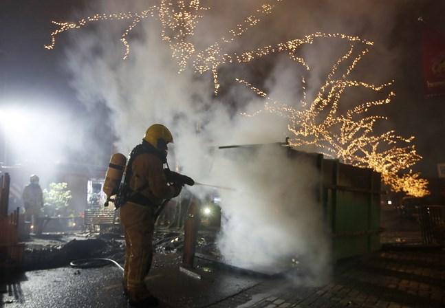 Räddningstjänsten släcker en container som satts i brand under protesterna mot utegångsförbudet.