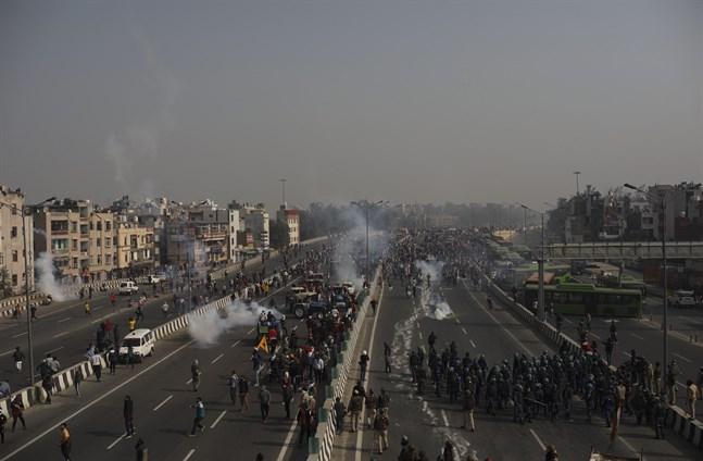 Polisen använder tårgas mot demonstranter som går in mot huvudstaden under republikens dag i New Delhi.