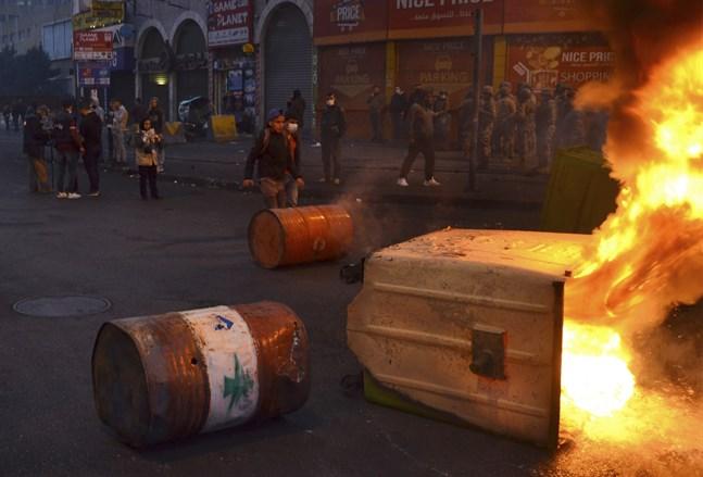 Demonstranter spärrar av en väg med tunnor och under protesterna på tisdagskvällen.