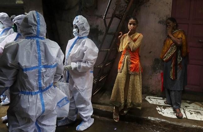 Hälsoarbetare genomför covid-19-screening på boende i slumområdet Dharavi i Bombay i Indien.