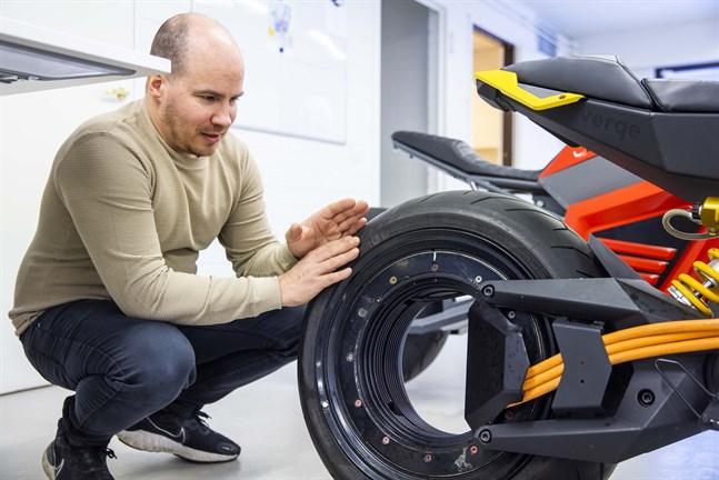 Tuomo Lehtimäki och mc:ns patenterade bakhjul. Fälgens yttre cirkel snurrar medan den inre står still. Tillsammans bildar de två delarna Verges elmotor.