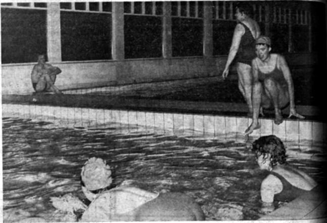 Simlärare Margita Sjöstrand på bassängkanten t.h. undervisar denna gång något äldre elever i simningens ädla konst.
