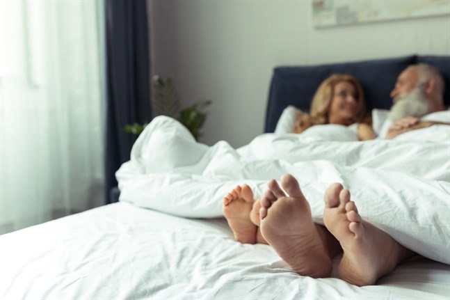Close-up view of feet of happy mature couple resting together in bed