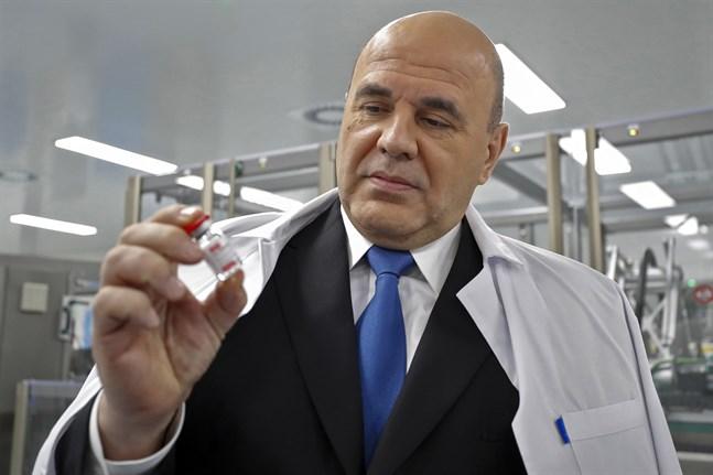 Rysslands premiärminister betraktar en dos av det ryska vaccinet Sputnik V vid en fabrik utanför S:t Petersburg. Bilden är från den 25 december.