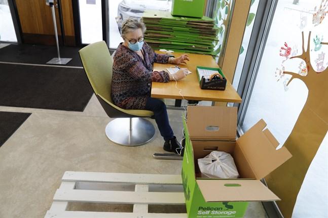Biblioteksassistent Riitta Konster förklarar hur bokåtervinningen fungerar.