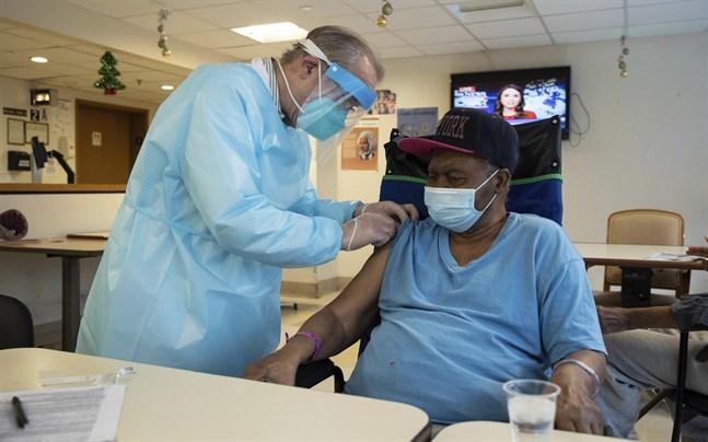 En person vid ett äldreboende i Harlem i New York får en vaccinspruta. Bild från januari.