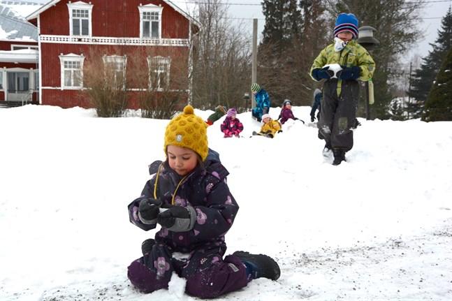 Emmie Holmberg studerar det nya elementet på dagisgården i Dagsmark. Axel Appelback bär på en snöbit som är gul av ökensand.