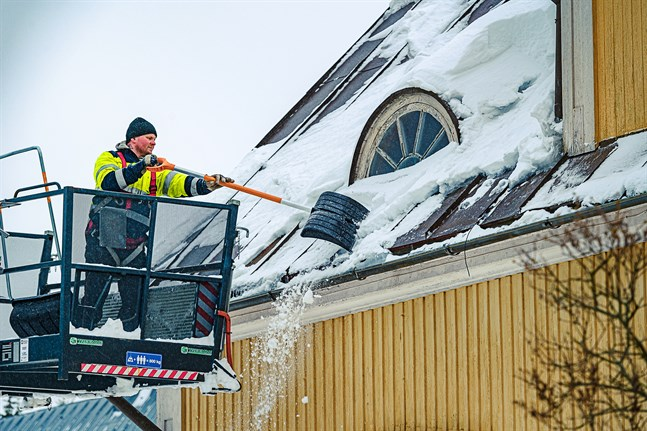 Alerte fixar snö och is från taken vid Vestersundsby skola i Jakobstad.