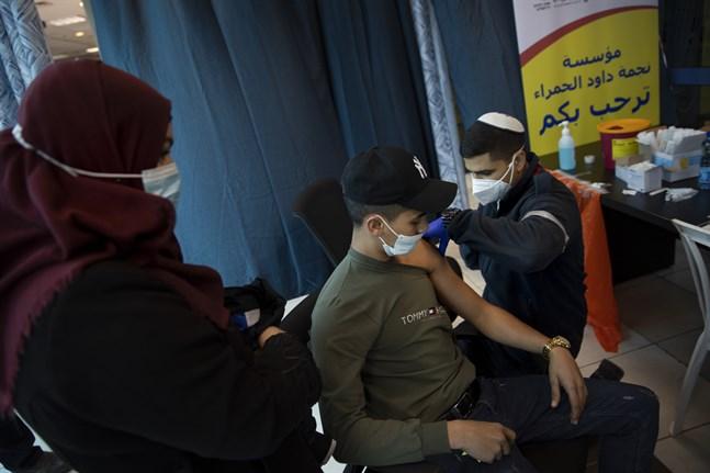 Ett israeliskt vårdlag ger vaccin till palestinier vid kontrollstationen Qalandia mellan Ramallah och Jerusalem.