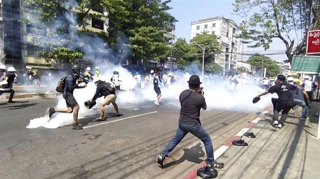 Polis i Rangoon använder tårgas mot demonstranter på måndagen.