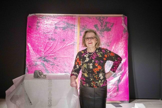 """Anne-Maj Salin med Marianna Uutinens forfarande inpackade målning """"Jungle Love"""" i bakgrunden. Verket hör till de nyförvärv som Kuntsis stiftelse gjort under 2010-talet, och kommer att visas på stiftelsens jubileumsutställning i Kuntsis museum."""