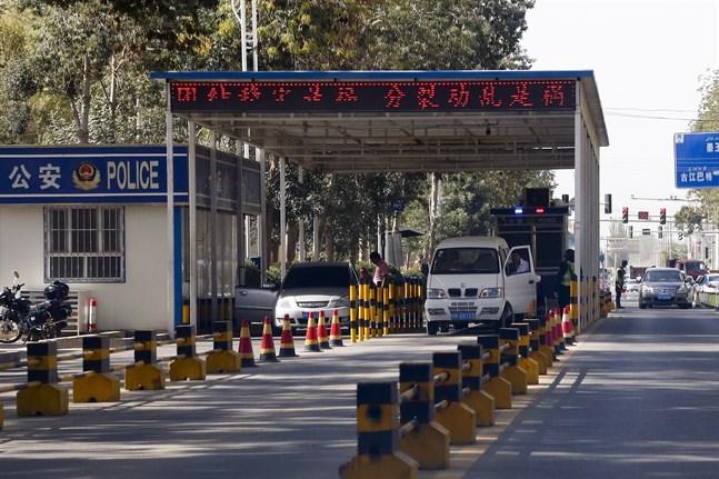 Uigurer får sina fordon kontrollerade vid en poliskontrollplats i Hotan i Xinjiang. Arkivbild.