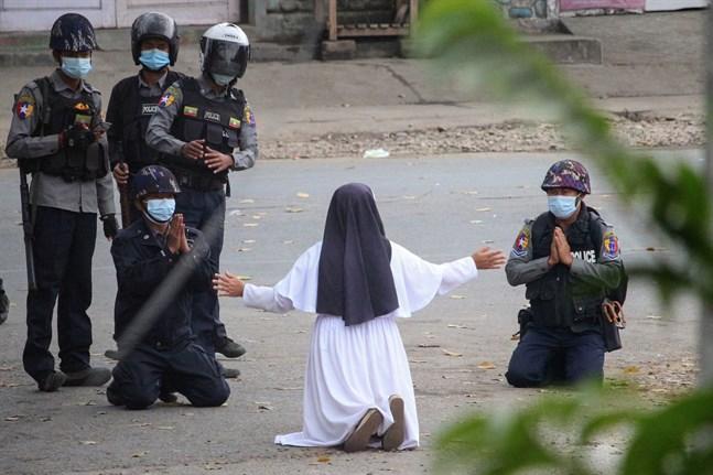 Ann Rose Nu Tawng knäböjer framför soldater i staden Myitkyina.