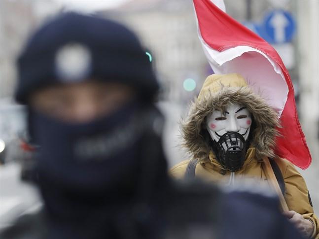 En man protesterar mot restriktionerna i Polen. Arkivbild.