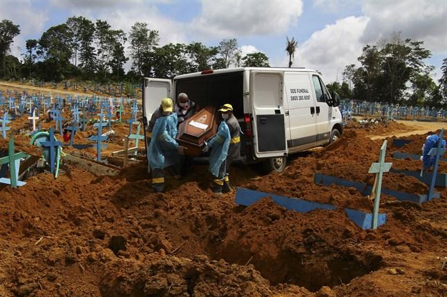 Begravningsarbetare i färd med att begrava en avliden covidpatient på en begravningsplats i Manaus i Amazonas i norra Brasilien. Bilden är från i januari.
