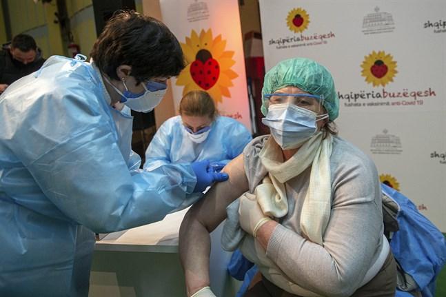 En albansk sköterska vaccinerar en läkare från grannlandet Kosovo med Astra Zenecas coronavaccin.