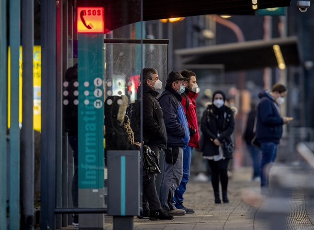 Tyskar i munskydd väntar på tunnelbanan i Frankfurt am Main.