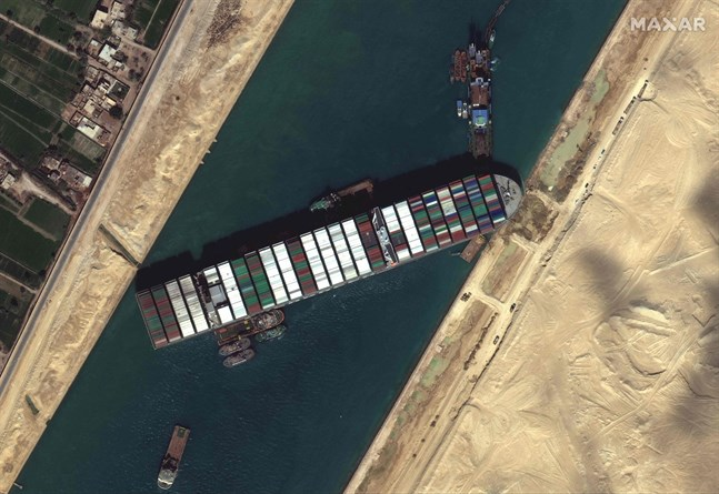 Bogserbåtar och grävare försöker bärga Ever Given, som kört på grund i Suezkanalen.