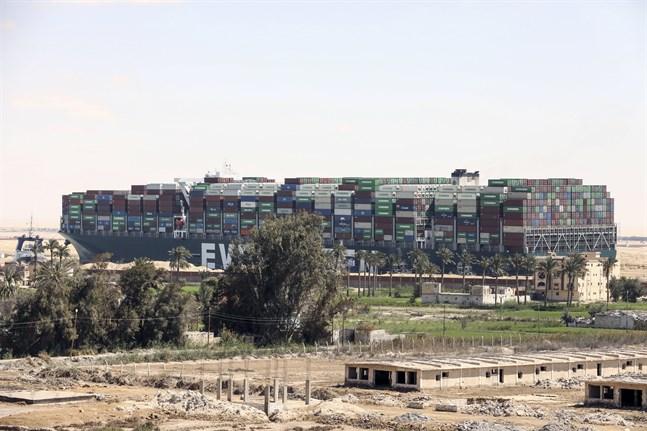 Jätteskeppet Ever Given tornar upp sig över det omgivande landskapet vid Suezkanalen.