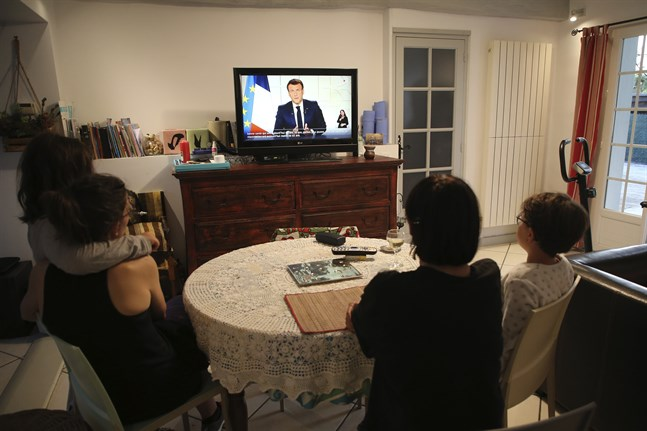 En familj lyssnar till Emmanuel Macrons tal.