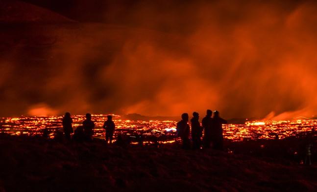 Besökare i Fagradalsfjäll på Island betraktar lava som strömmar från vulkanen.