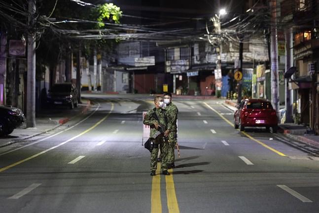 Beväpnade soldater bevakar en tom gata i Metro Manila, Filippinerna, efter att utegångsförbudet trätt i kraft.