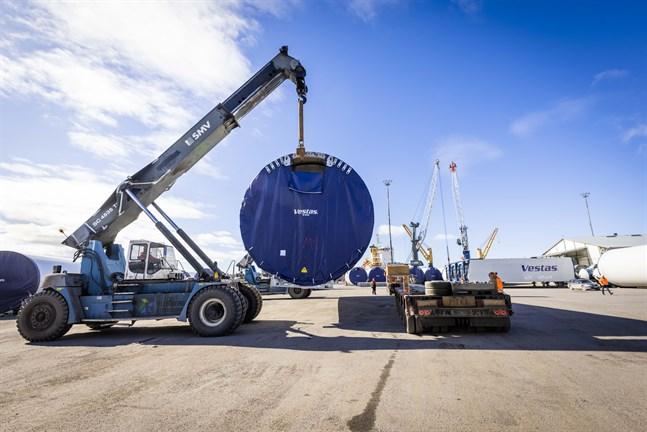 Långtradarekipaget står redo i hamnen och en del av ett vindkraftstorn lyfts på plats av två teleskoplastare.