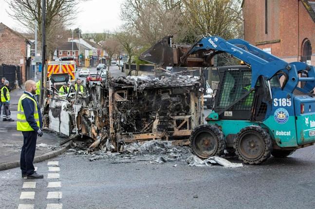 Stadens anställda städar upp efter nattens oroligheter. Här är det en buss som stuckits i brand, som forslas bort från Shankill Road i Belfast.