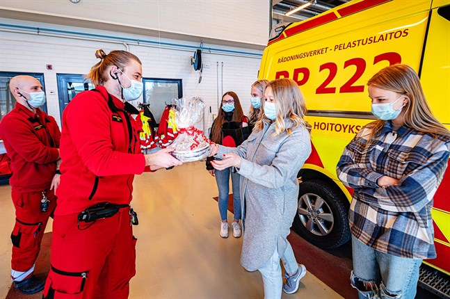 Akutvårdarna Daniel Pettersson och Henrik Mård tar emot kakor och vetevärmare av niondeklassarna Sheila Kung, Noomi Enlund, Minea Sacklén och Julia Gunnar.