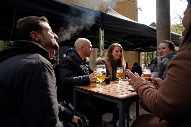 Upp till sex personer får samlas tillsammans utomhus. Det här sällskapet njuter på en uteservering i östra London.