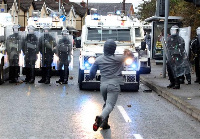En bild som väcker oro. Demonstrant och poliser på Nordirland.