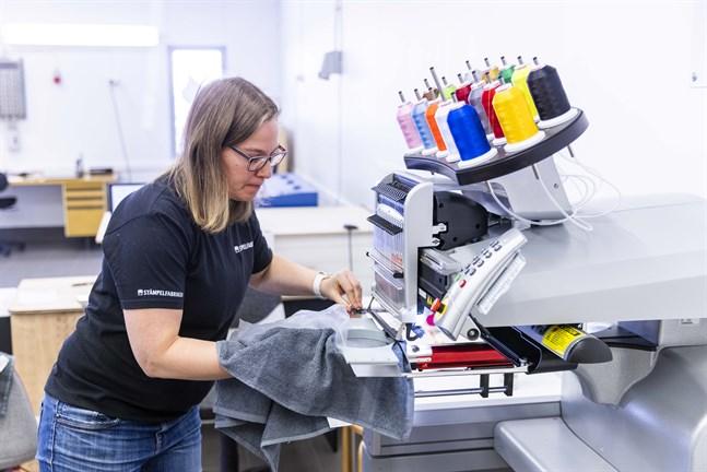 Jenni Ribacka och hennes man Mats tog över Stämpelfabriken i november. Numera gör företaget också tryck och broderier. Här broderar Jenni ett namn på en handduk med hjälp av den nya maskinen.
