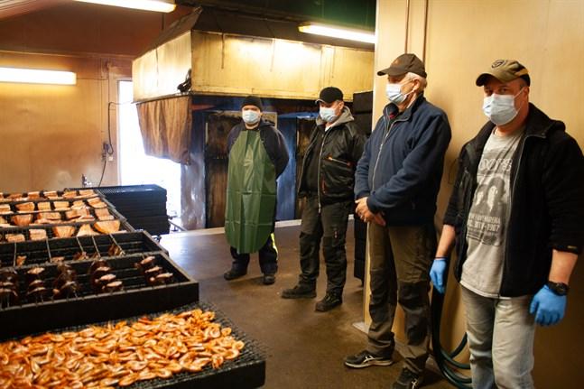 Stefan Smedman, Thomas Sund, Ole Lundberg och Mats Eriksson betraktar dagens arbete. Den nyrökta fisken ska snart leta sig bort från rökeriet till kunderna.