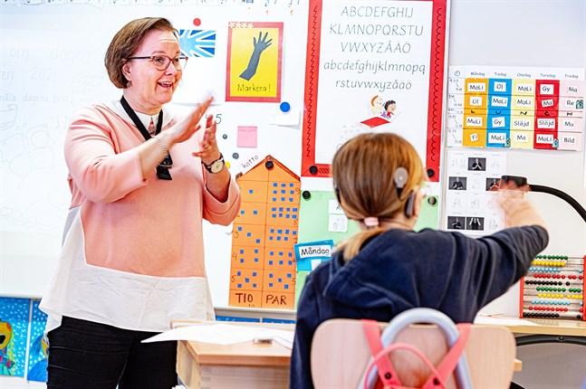 Med hjälp av stödtecken berättar Tina Granvik-Storbacka om vad som ska hända i skolan kommande vecka.