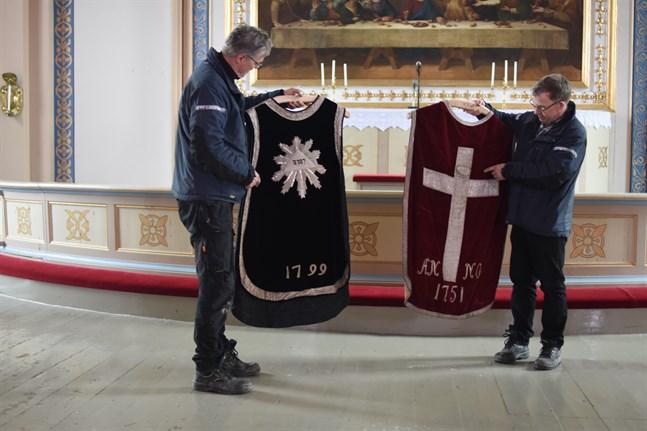 Olav Klemets och Kenneth Bergqvist inspekterar de gamla mässhakarna i Lappfjärds kyrka.