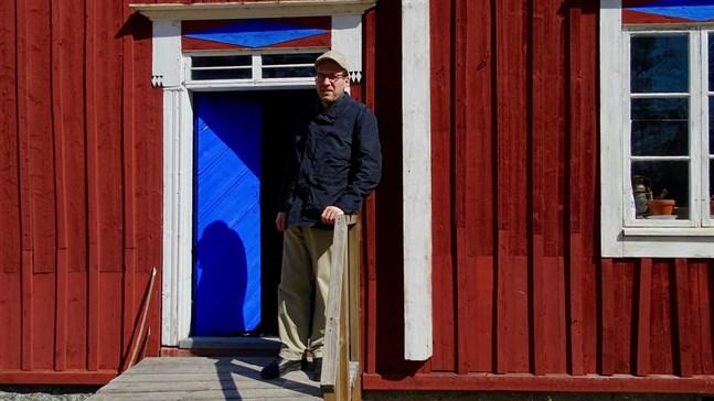 """Daniel Beijar, verksamhetsledare för Replot hembygdsförening, vid Granösunds fiskeläge i Södra Vallgrund. Stugan som """"Svennas Sven"""" bodde i är det senaste tillskottet av byggnader på museiområdet."""